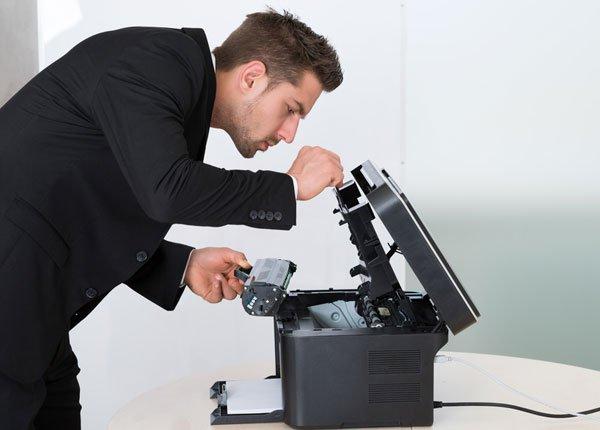 Man adding toner cartridge to printer